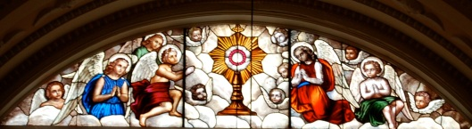Eucharist stained glass window behind altar
